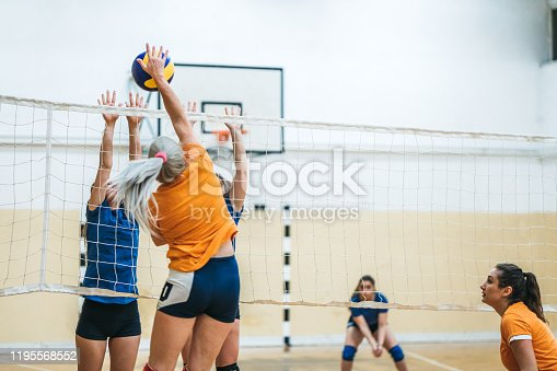 Female young caucasian volleyball player spiking the ball at game.