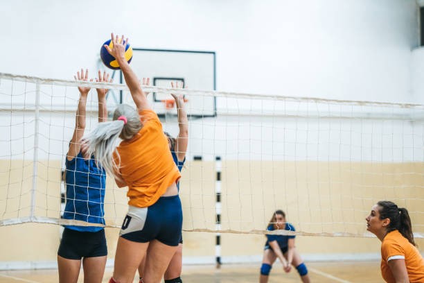 Female volleyball player spiking the ball stock photo