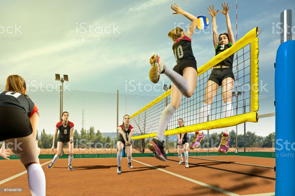 Female volleyball players having match in sunny day stock photo