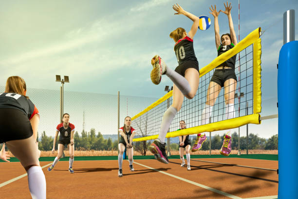 Female volleyball players having match in sunny day Female volleyball gameplay action in sunny day spiked stock pictures, royalty-free photos & images