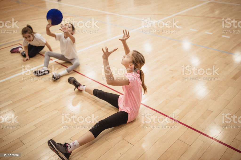 Female volleyball team exercising indoors on volleyball court