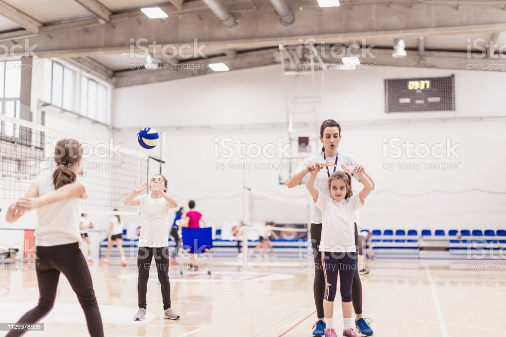 Female volleyball team exercising with coach