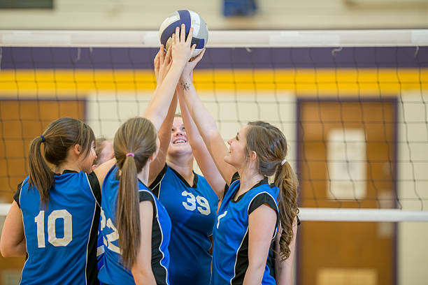 female volleyball team huddle - volleyball sport stock photos and pictures