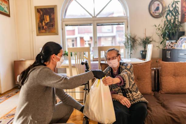 집에서 노인 여성에게 식료품을 가져오는 여성 자원 봉사자 - 팬데믹 질병 뉴스 사진 이미지