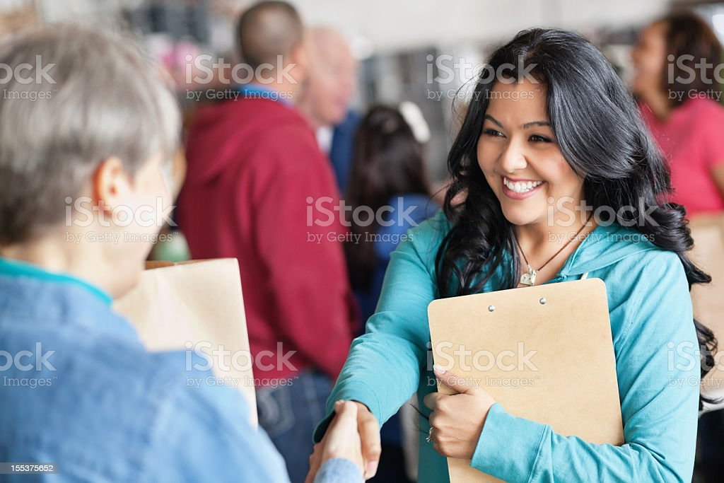 Female volunteer greeting woman at donation facility stock photo