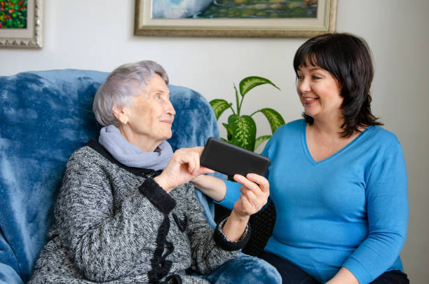 Female volunteer is happy to help an elderly woman use a smartphone stock photo