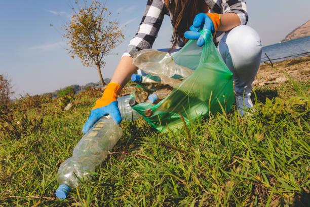 Mujer voluntaria recogiendo basura plástica al aire libre. Entorno y salvar el concepto de tierra. - foto de stock