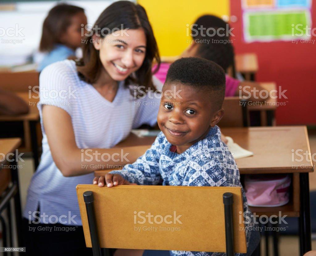 Female Volunteer teacher and elementary school boy smiling to camera stock photo