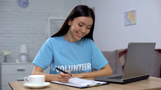 Female volunteer working laptop and writing notes sitting table, charity project stock photo