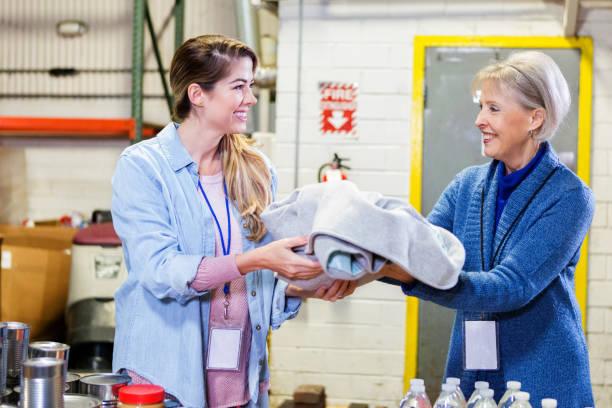 femmes volontaires travaillent dans la banque alimentaire - équipement domestique photos et images de collection