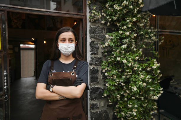 female waiter with a protective mask in front of the café - small business saturday stock pictures, royalty-free photos & images