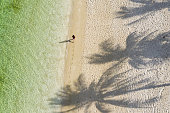 Female walking along perfect beach with palms and clear water, early morning Rote Island, Indonesia