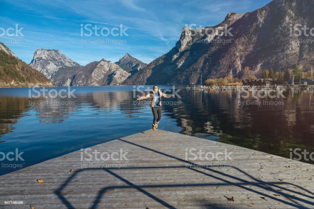 Female wanderlust jumping on dock stock photo