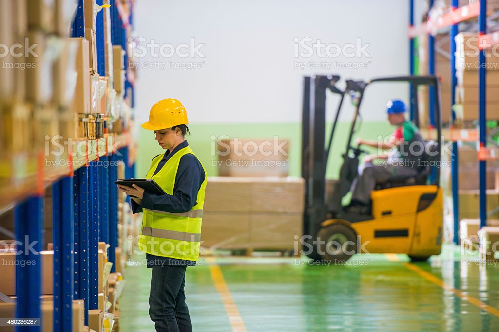 Female Warehouse Employee Doing A Checklist stock photo