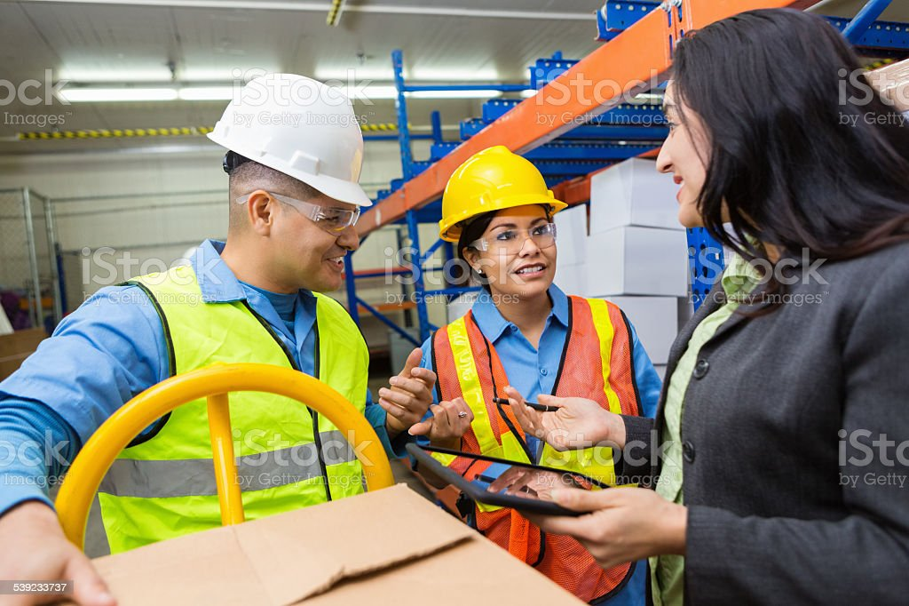 Female warehouse supervisor talking with blue collar workers stock photo