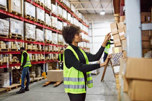 vrouwelijke magazijnmedewerker stapelen van vakken op het rek - warehouse worker stockfoto's en -beelden