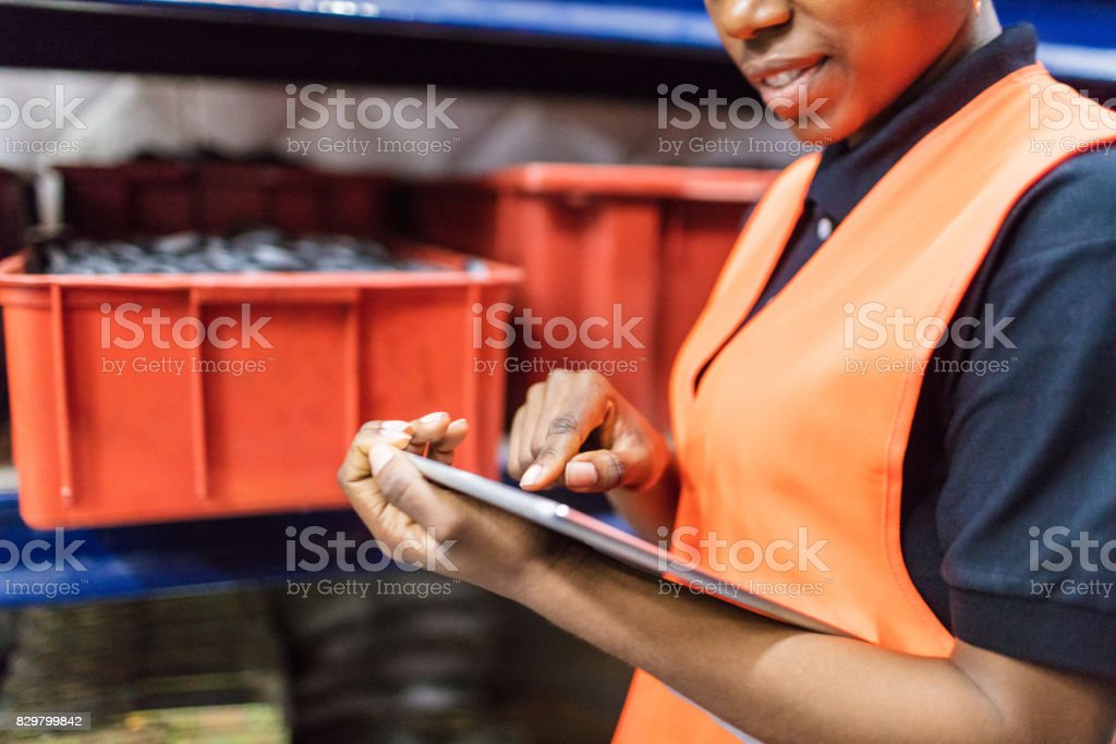 Female warehouse worker using digital tablet stock photo