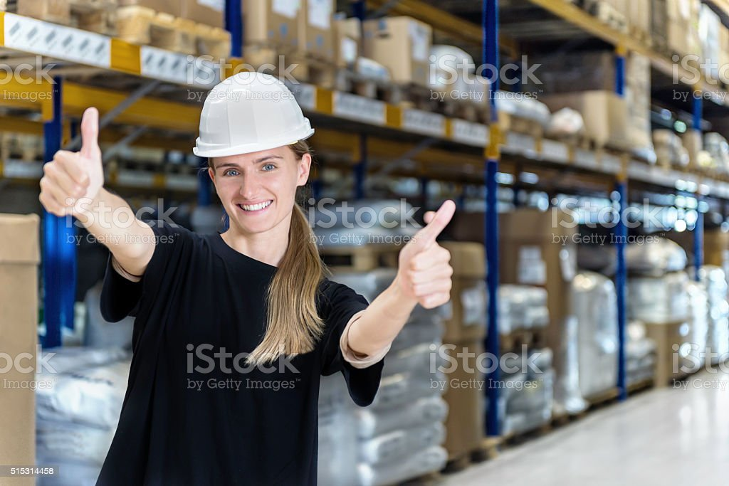 Female warehouse worker with thumbs up stock photo
