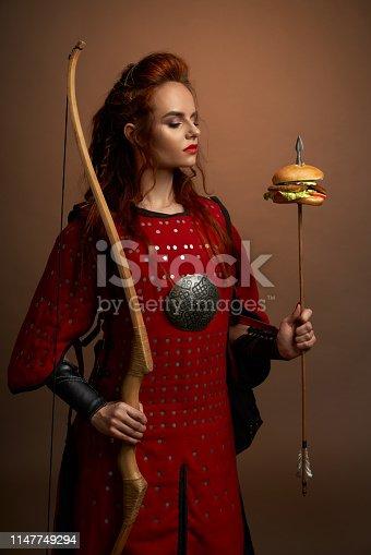 istock Female warrior holding arrow with hamburger, posing. 1147749294