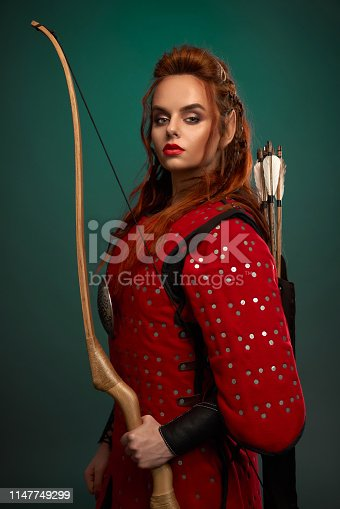 istock Female warrior posing with bow and arrows. 1147749299