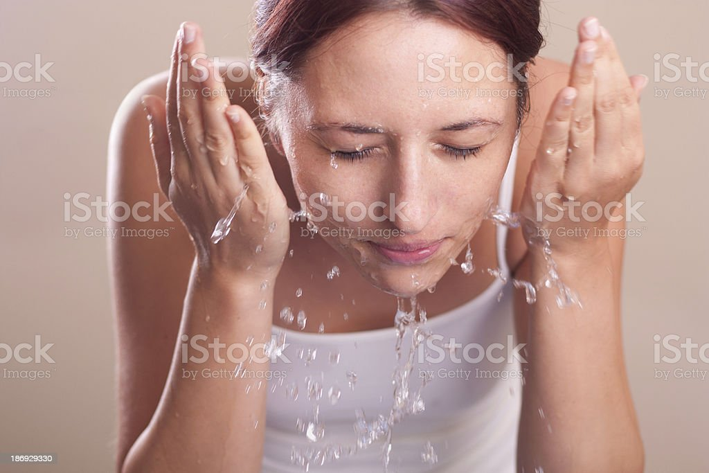 female washing her face with water stock photo