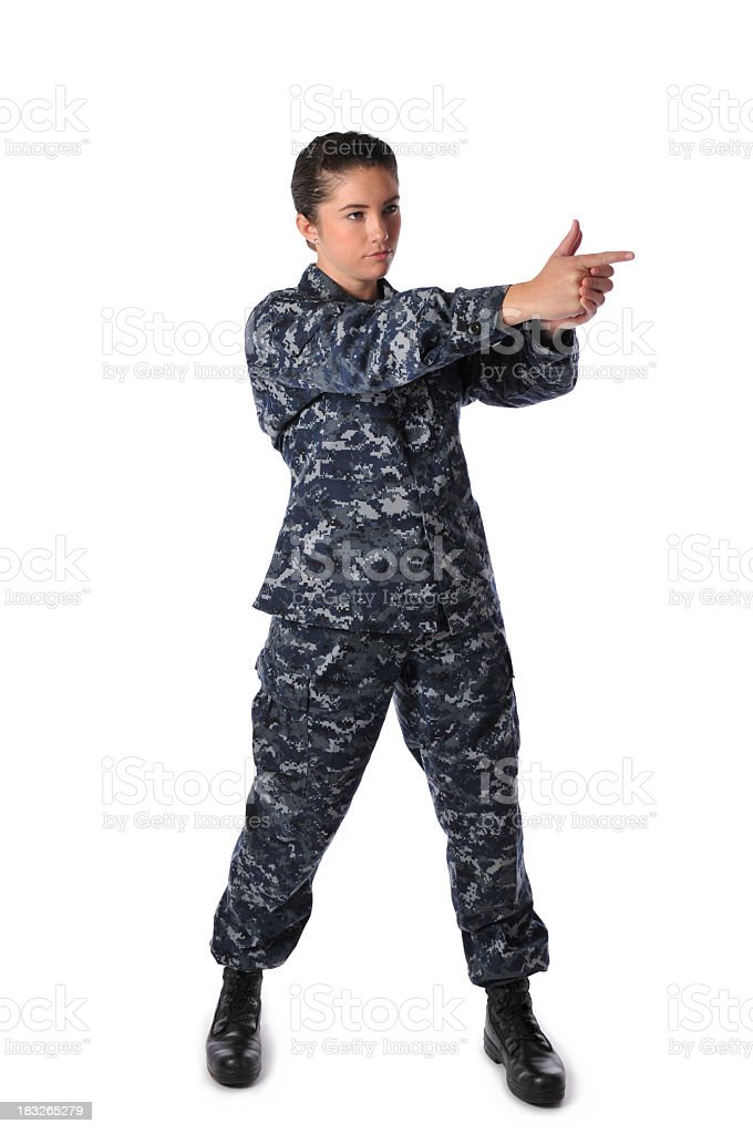 Female wearing blue Navy fatigues, pretending to hold a gun. stock photo