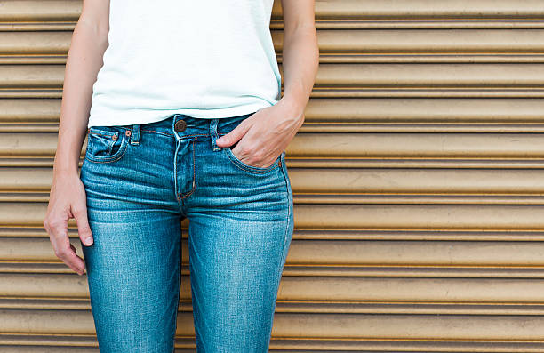 Female wearing jeans Close up of female wearing blue denim jeans.  hands in pockets stock pictures, royalty-free photos & images