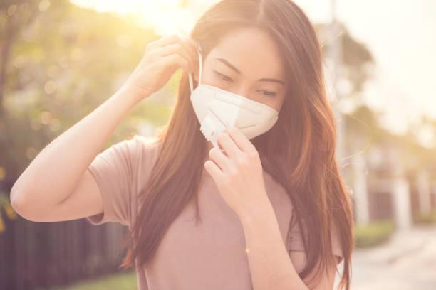 female wearing n95 respiratory protection mask against air pollution. healthcare concept. - febbre russa foto e immagini stock