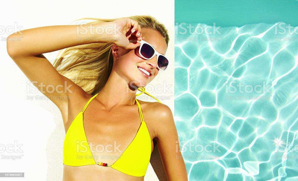 Female wears sunglasses and bikini lying by pool royalty-free stock photo