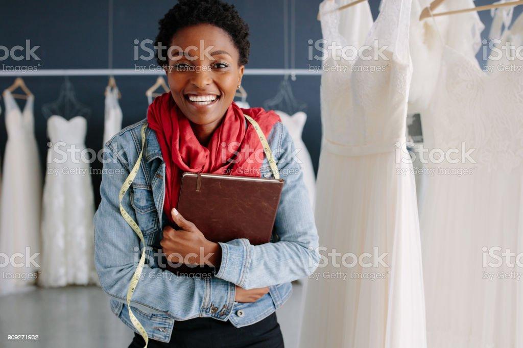 Female wedding fashion designer in a bridal boutique stock photo