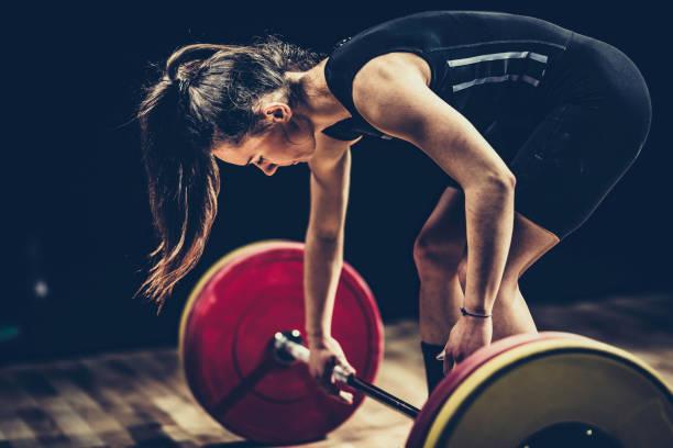 Weiblicher Gewichtheber bereitet sich auf einen Deadlift vor – Foto