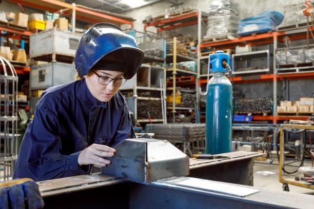 Female Welder Inspecting Her Work stock photo