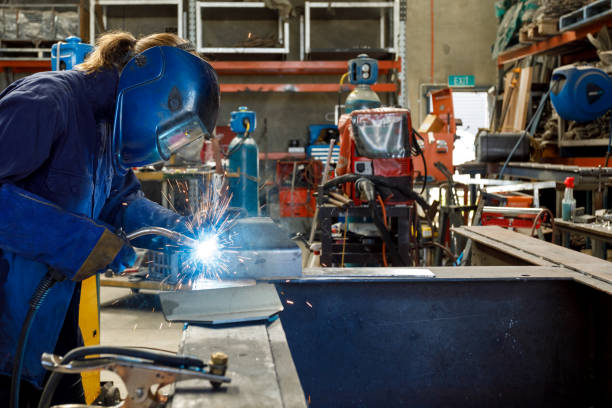Female Welder Young Female Welder Working In Factory Wearing Protective Safety Gear metal worker stock pictures, royalty-free photos & images