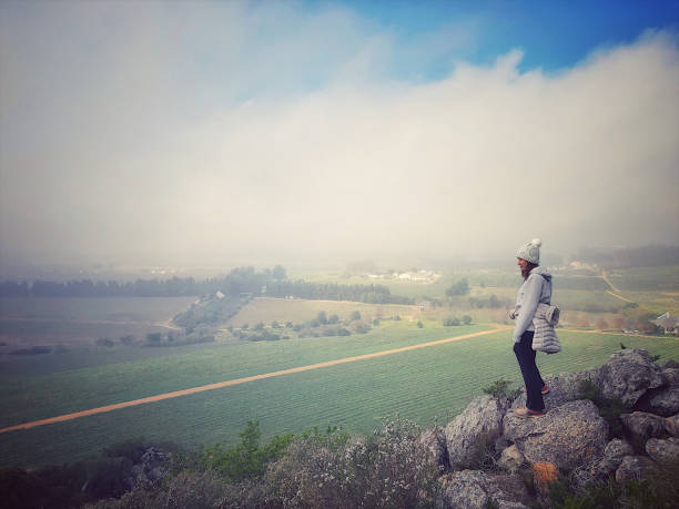 Female winemaker looking down from a rocky outcrop towards resting vineyard in winter stock photo