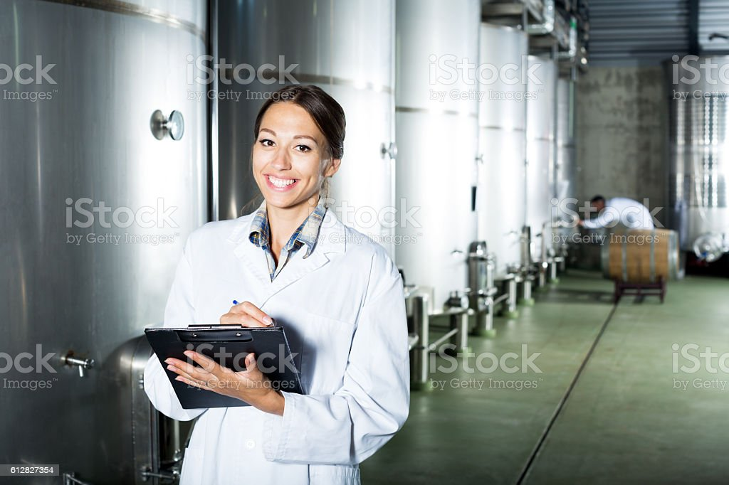 Female winery employee in uniform taking off data stock photo