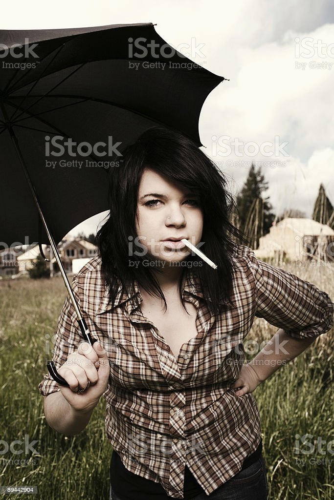 Female with Ciggerette Holding Umbrella royalty-free stock photo