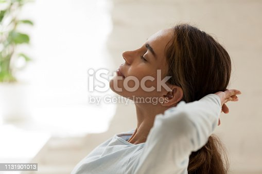 istock Female with closed eyes putting hands behind head resting 1131901013
