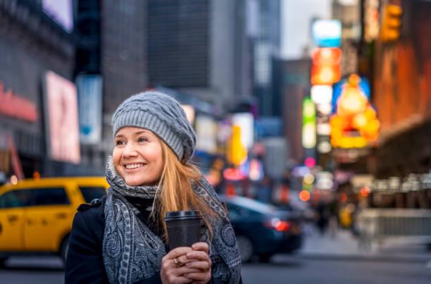 wanita dengan kopi di times square di nyc. - traveler new york potret stok, foto, & gambar bebas royalti