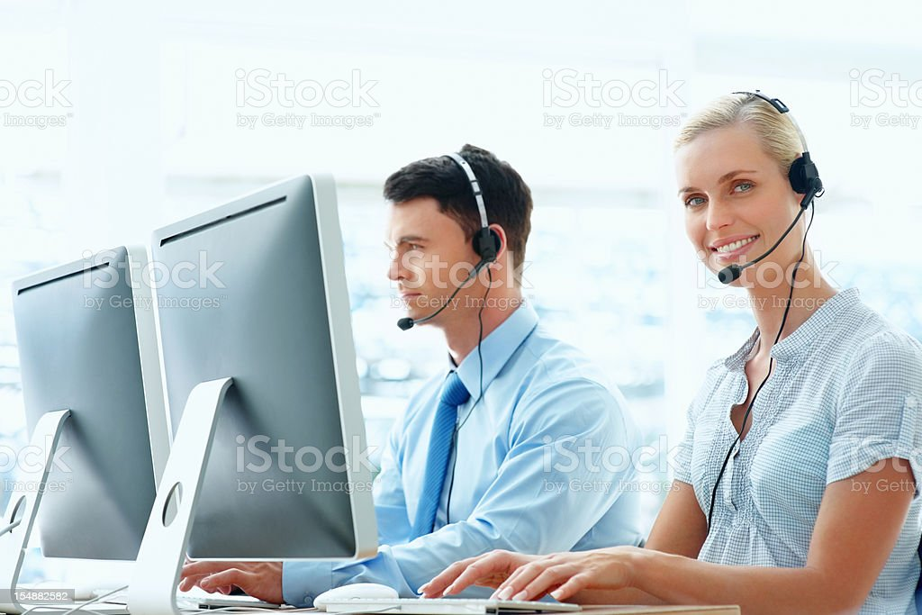 Female with colleague wearing headset and working on computer royalty-free stock photo