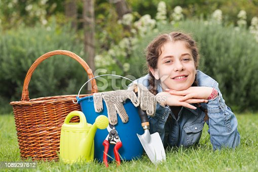 istock female with gardening tools while lying in park 1089297612