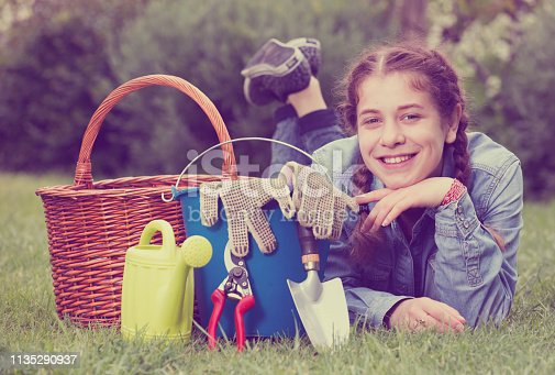 istock female with gardening tools while lying in park 1135290937