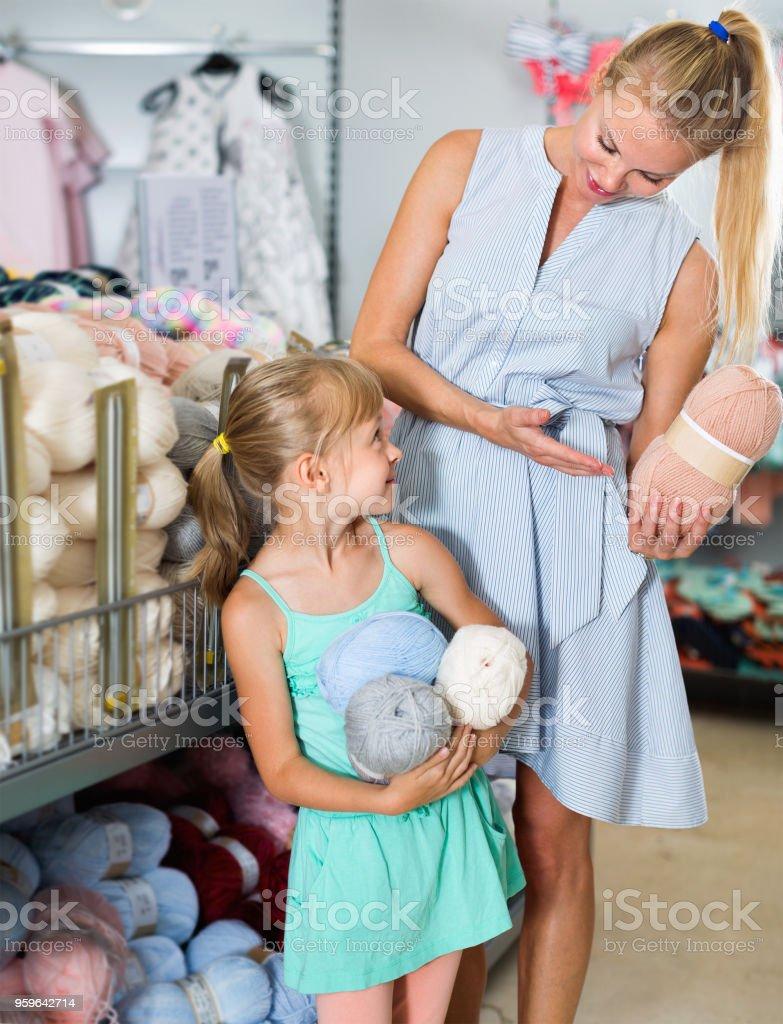 Mujer con niña en la tienda elegir hilo para tejer - Foto de stock de Adulto libre de derechos