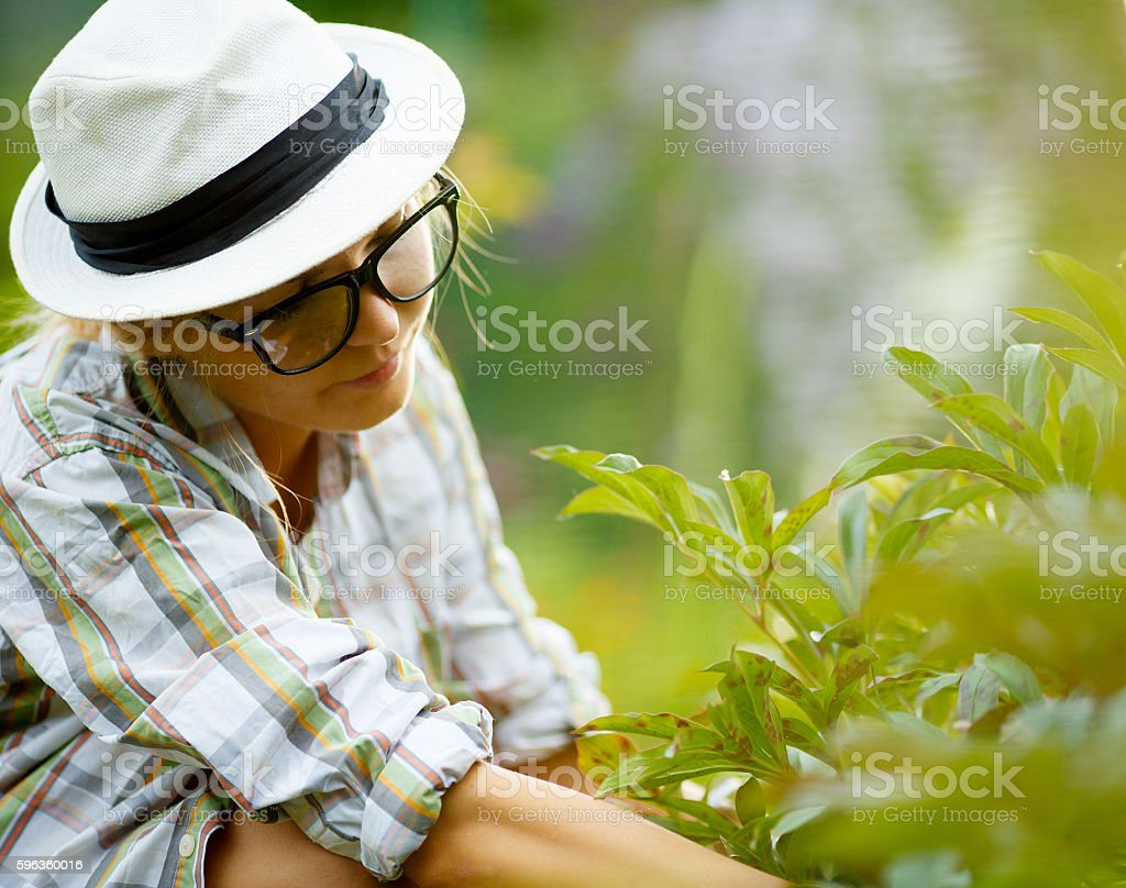 female with glasses and hat touching plants royalty-free stock photo