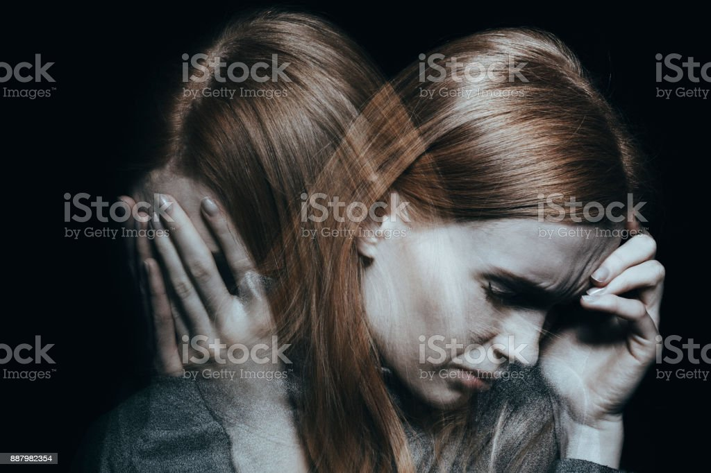 Female with mood disorder Young red haired female with mood disorder crying and having a headache Addiction Stock Photo