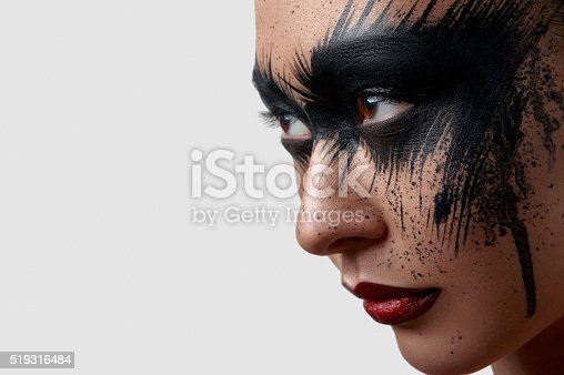 istock Female with Paint on Face looking at the Side 519316484