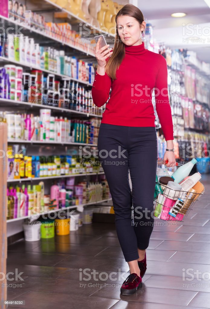Female with phone in cosmetics store royalty-free stock photo