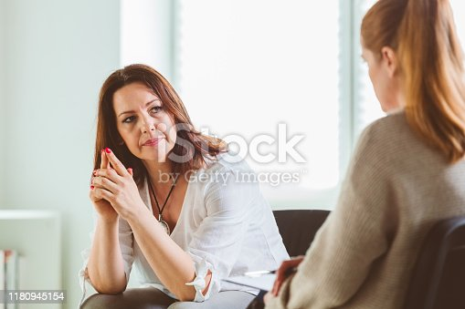 Mature female sharing problems with psychotherapist. Mental health professional is listening to woman during therapy session. They are at community center.