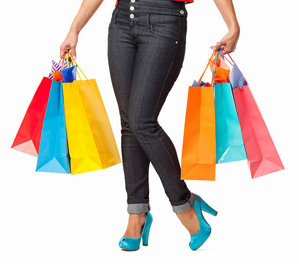 Female With Shopping Bags - Isolated Low section of female in skinny jeans carrying multi colored shopping bags. Horizontal shot. Isolated on white. skinny jeans stock pictures, royalty-free photos & images