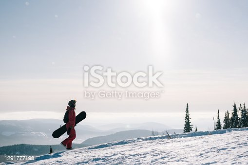 Female with snowboard. Snowboarder walking on snowy slop watching beautiful atmospheric mountain landscape