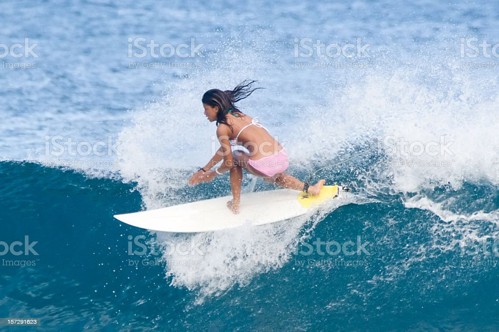 Female with tanned skin surfing a wave stock photo